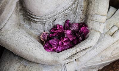 A photo of a Buddha statue holding flowers